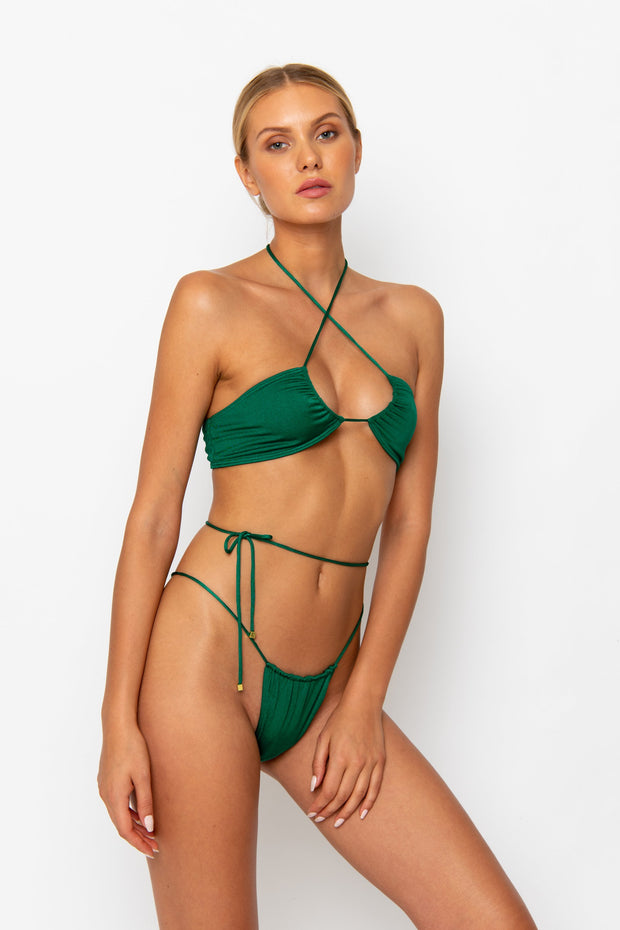 Sommer Swim model facing sideways to the left and wearing a Naomi tie side bikini bottom in Emerald