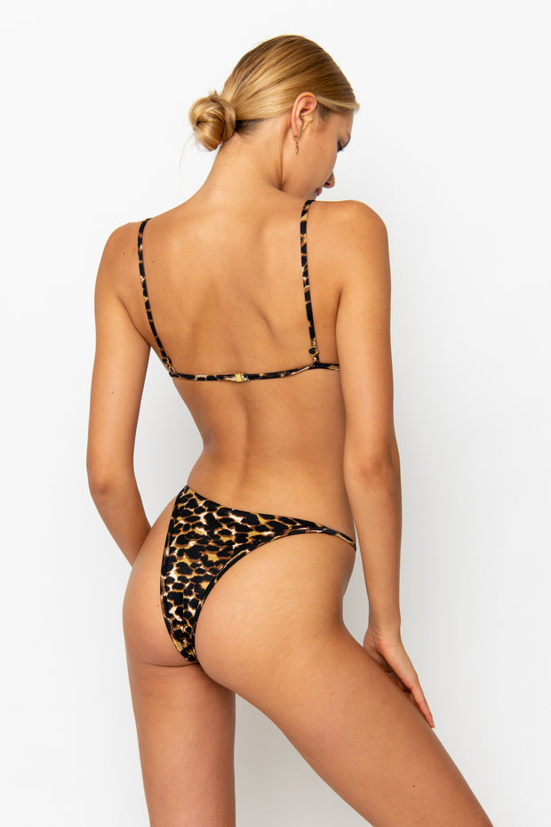 Sommer Swim model facing backwards and wearing a Uma bralette bikini top in Leopard Luxe