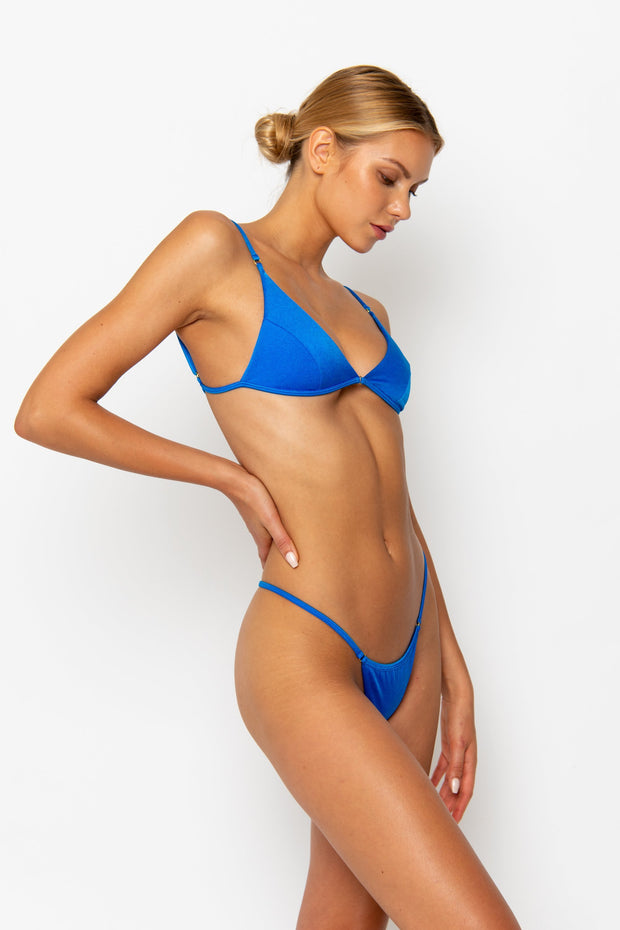 Sommer Swim model facing sideways to the left and wearing Uma bralette top in Sirius