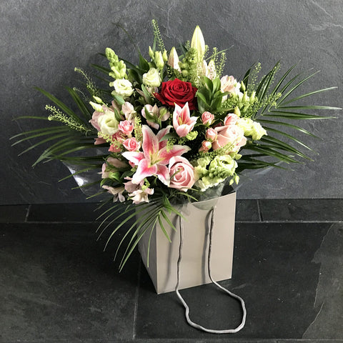 Mixed bag of flowers in oasis with Luxury Red Rose ( if available) in gift bag