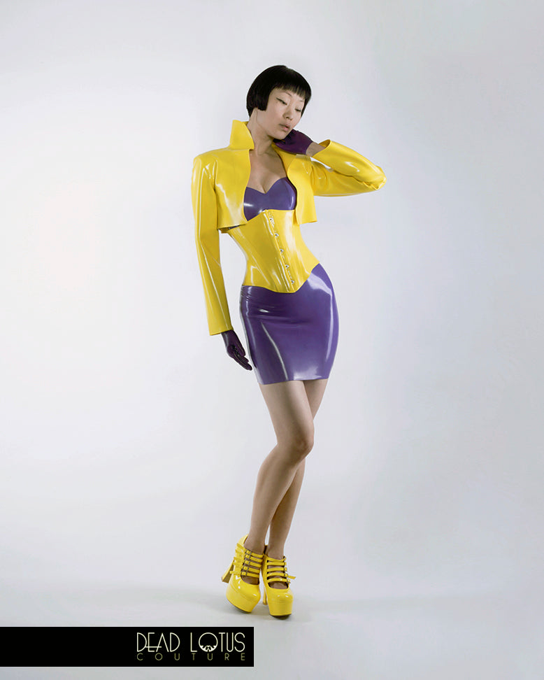 Yellow latex PLUVIA Bolero Jacket worn by model with collar up, a mini dress, corset and wrist gloves by Dead Lotus Couture