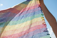 Pastel rainbow keffiyeh by Tahrir Scarf in classic white (flying)