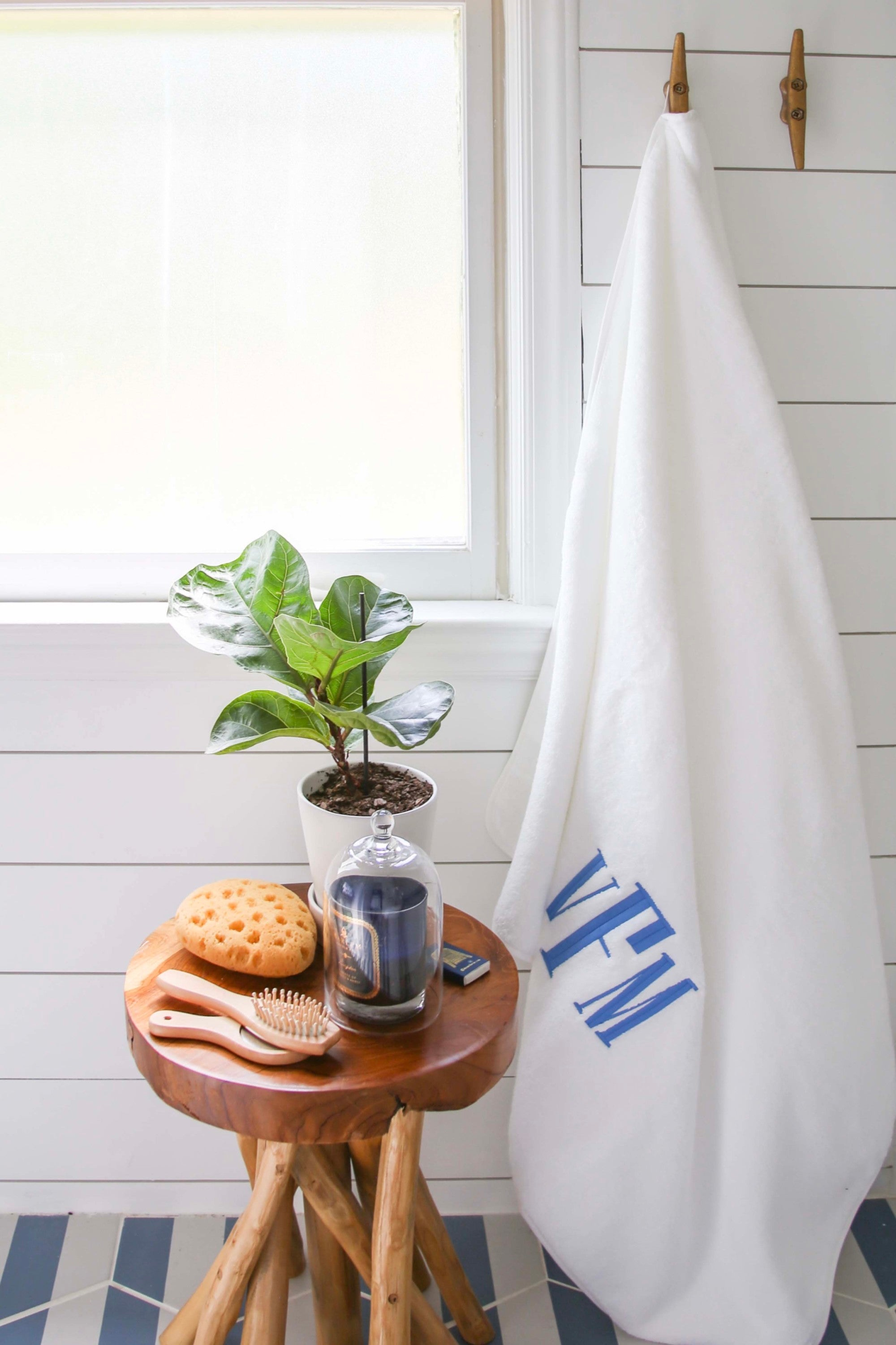 This nautical kids bathroom is packed with small bathroom remodel ideas. These decorative details include monogrammed towels, painted shiplap, and greenery. The paint is Fresh Kicks by Clare.