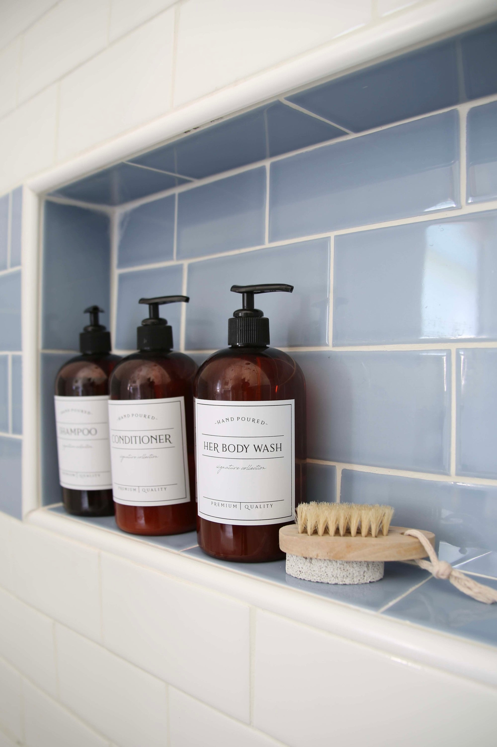 This nautical kids space is packed with small bathroom remodel ideas. Here, blue and white shower tiles are paired with the perfect decor pieces and decorative shampoo and conditioner bottles.