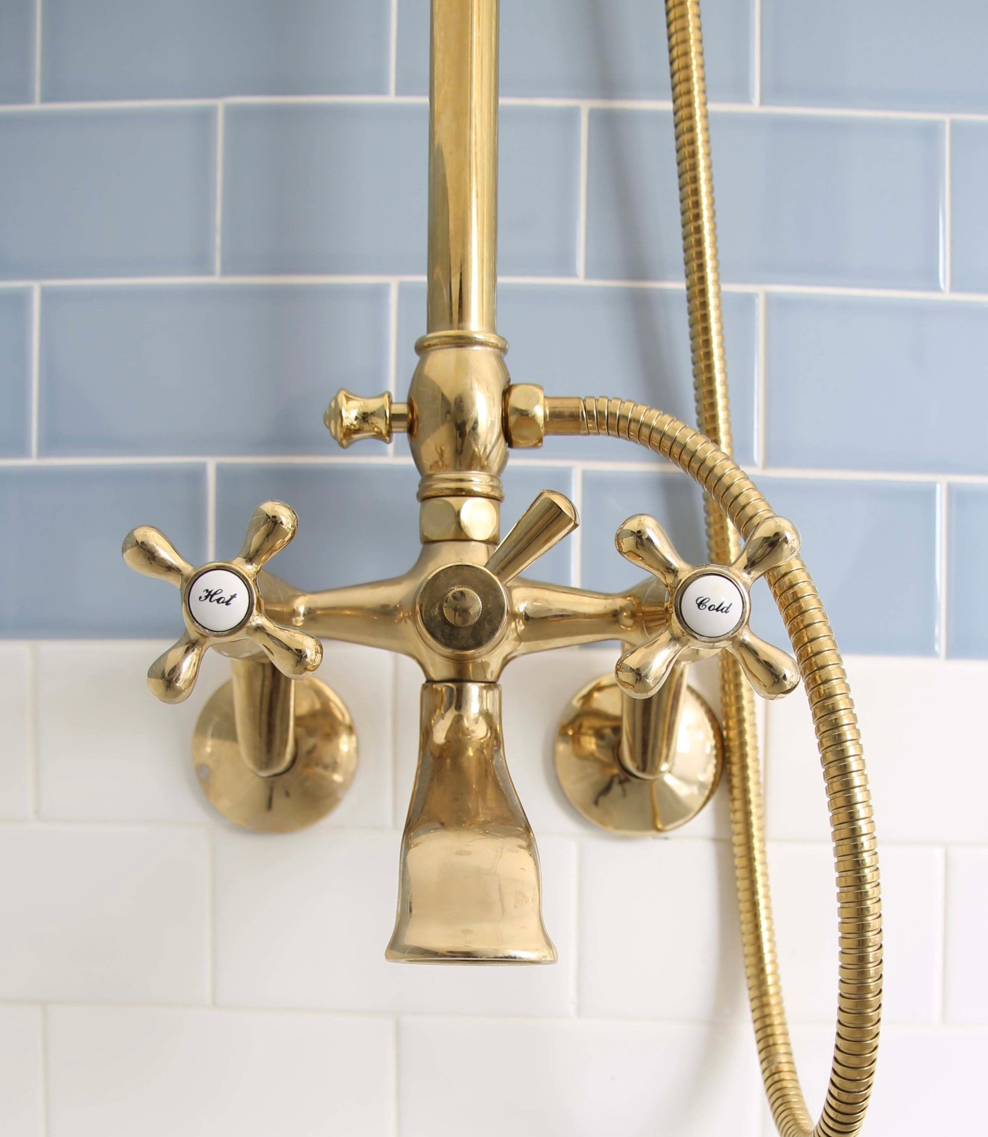 To truly tie the theme together in a nautical bathroom, swap your fixtures. This blue and white kids bathroom features gold vintage fixtures.