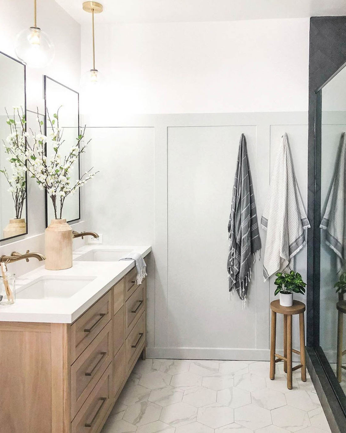 A fresh coat of light greige paint — Penthouse by Clare — plus a restructured layout and a gorgeous black shower took this bathroom from dated to elevated.