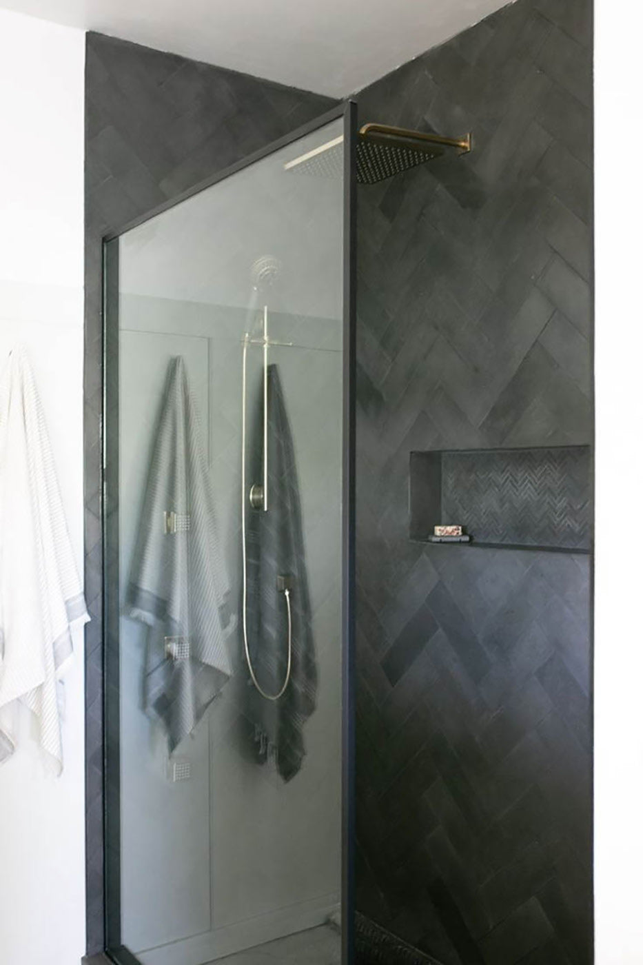 This luxurious black herringbone tiled shower replaced a once-dated bathtub in this couple's master bathroom See the full makeover, featuring Penthouse paint by Clare, now!