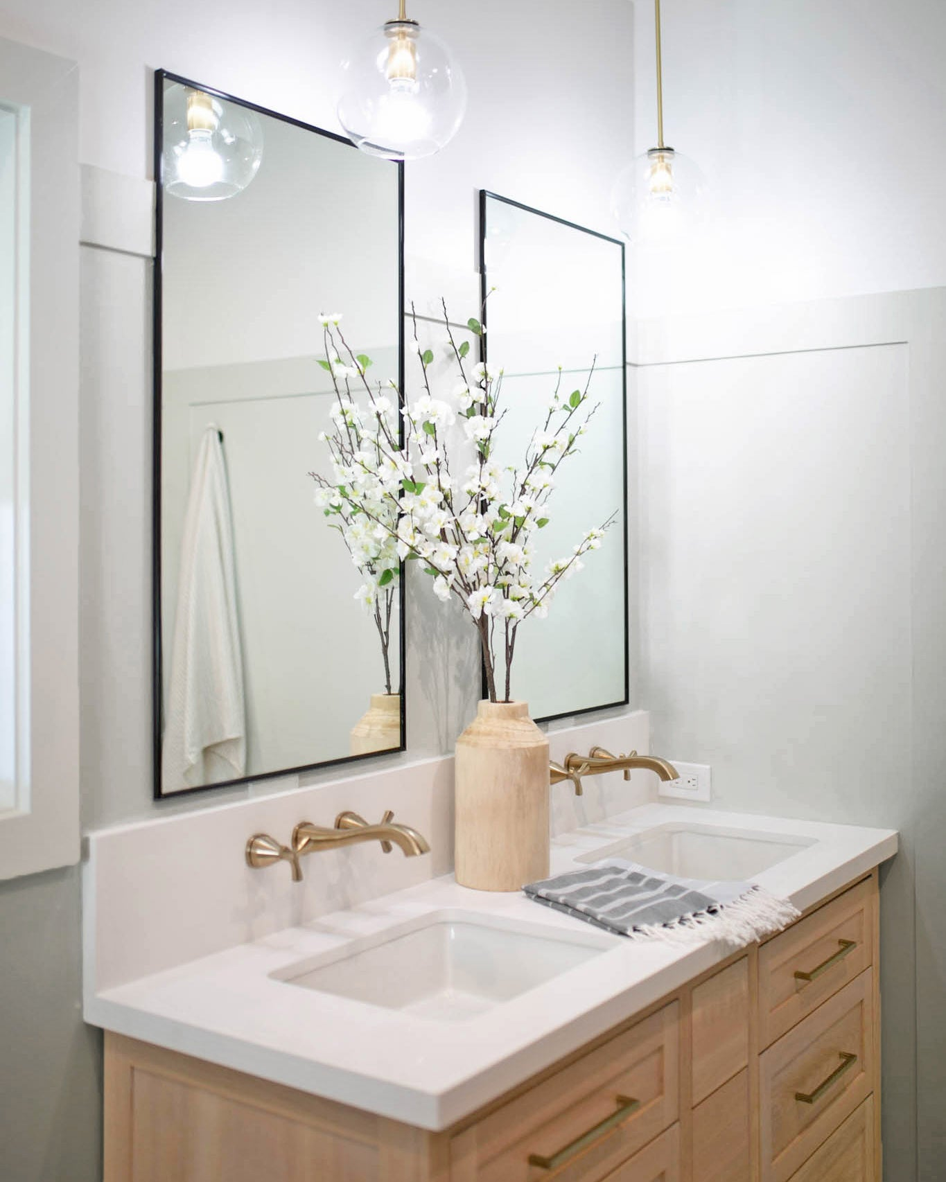 This main bathroom uses a light greige paint to create a calming vibe. The light gray paint color is Penthouse by Clare.