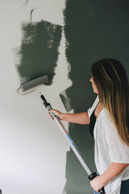 Elizabeth Rishel of the blog Within the Grove painting a green accent wall in her kids room. Bedroom accent wall color is Current Mood by Clare.