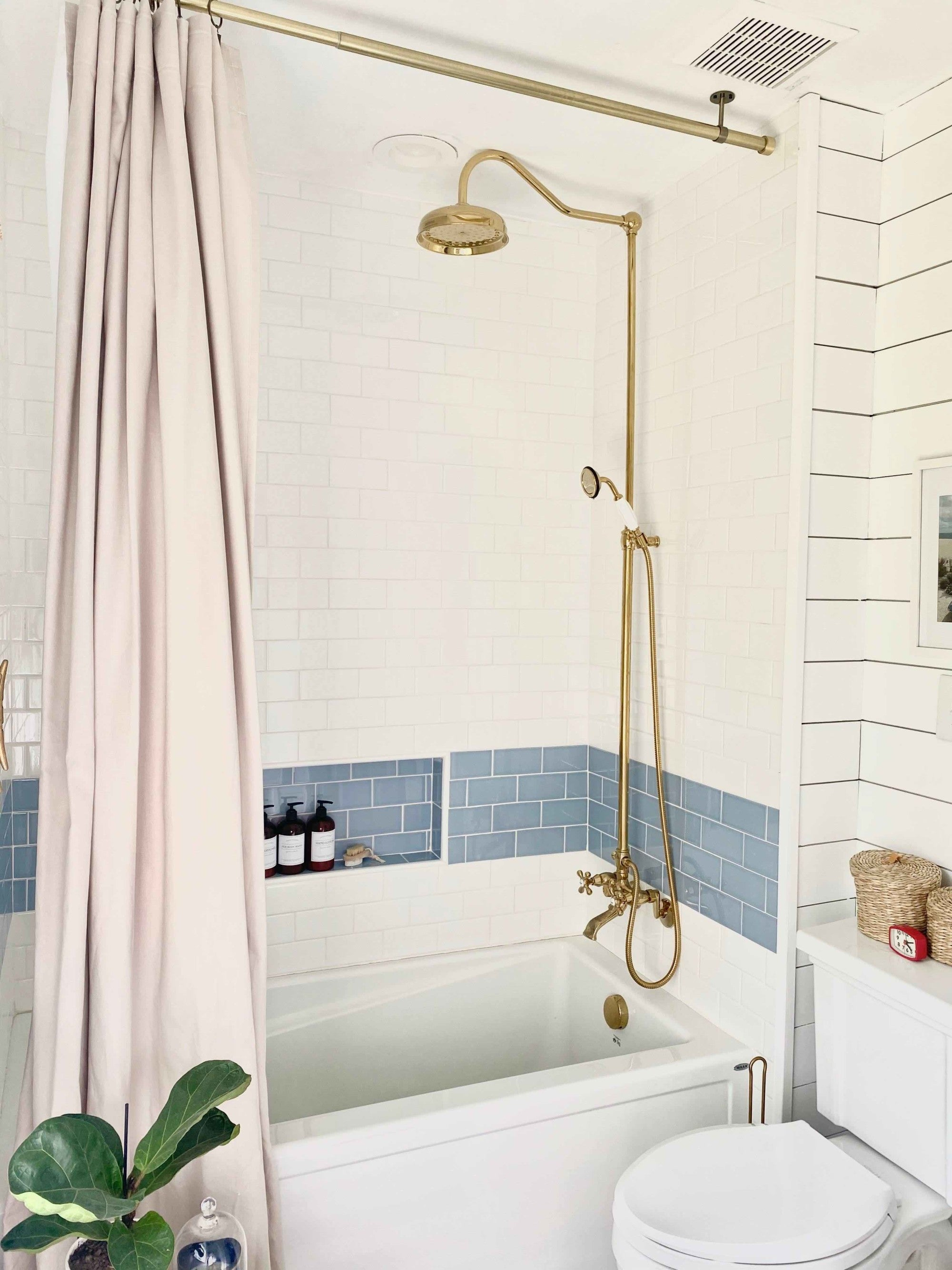 This kids bathroom took on a nautical theme with vintage fixtures including a gold shower head and painted sink. The blue and white tile is complemented by horizontal shiplap painted with Clare's Fresh Kicks white paint.