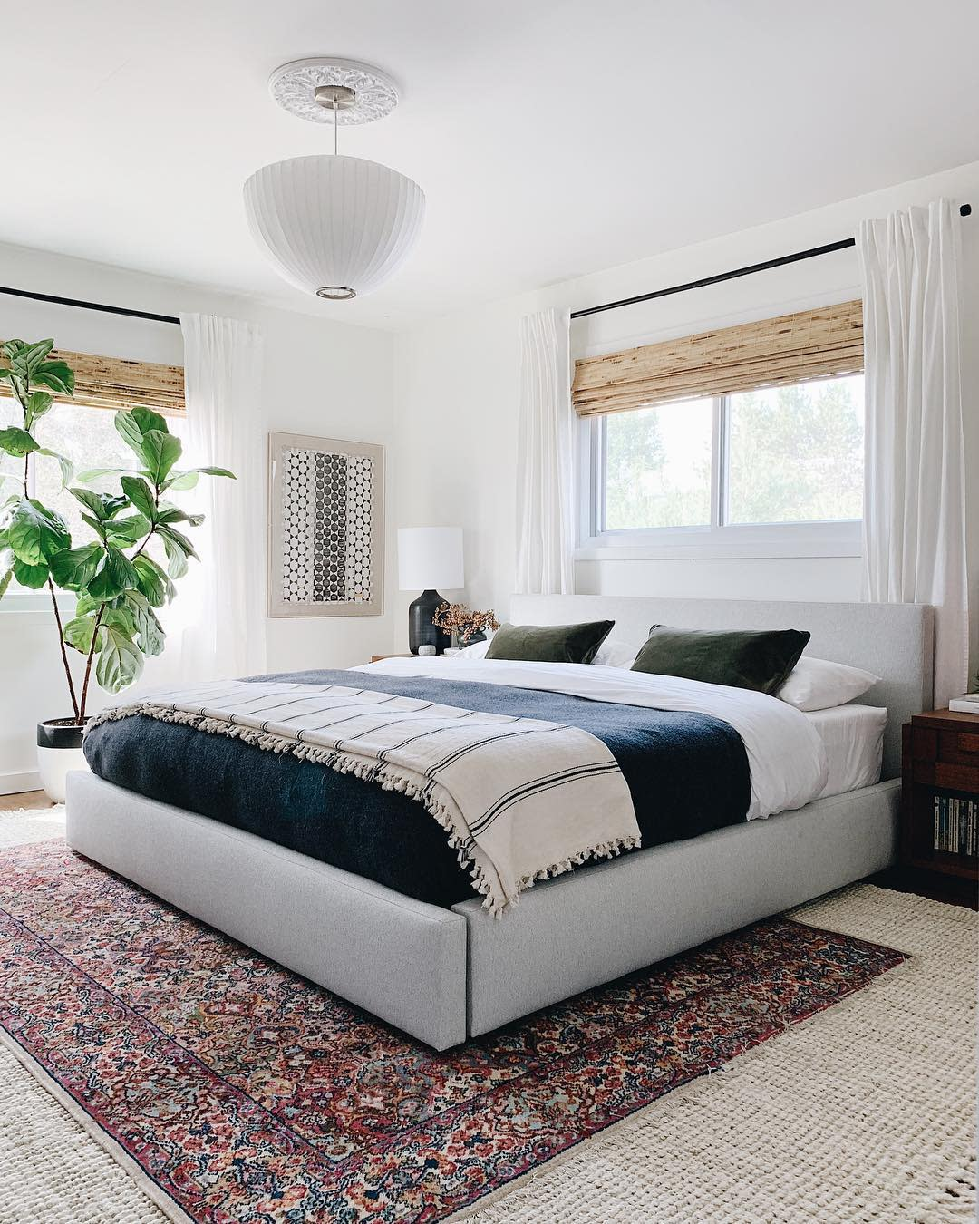 White Walls painted in Whipped, a warm white paint color by Clare, make this bedroom feel warm and inviting.  Lots of texture and plants add a cozy vibe.