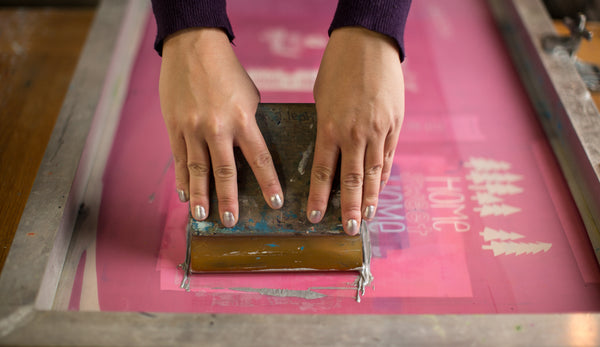 hands using a squeegee screenprinting