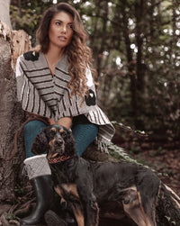 Woman relaxing in the forest and walking her dog wearing Táabal Flowers Poncho by 32 Estados