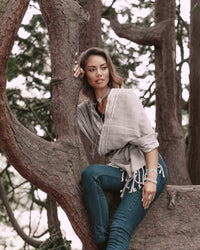 Curious woman exploring sitting on a tree wearing Táabal Rebozo Grey Shawl Wrap by 32 Estados