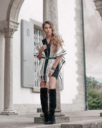 Confident woman leaning on a pillar wearing Táabal Black & White poncho for going out