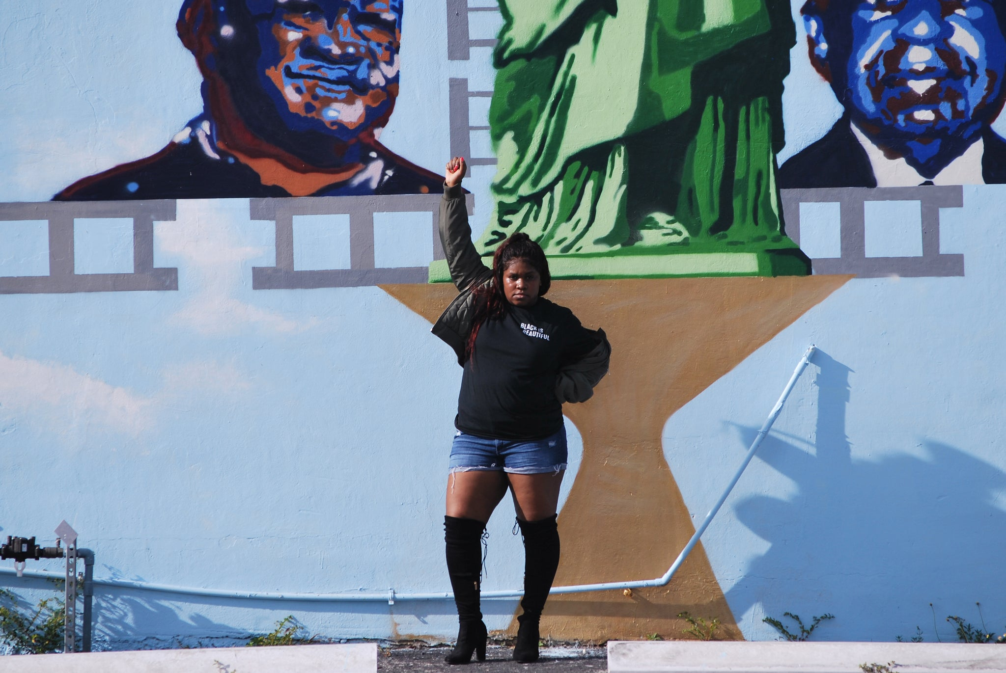 Model rocking the Black is Beautiful T-Shirt with Knee High Boots and the solidarity fist