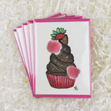 Chocolate cupcake with chocolate frosting and a strawberry, five handmade cards with envelopes