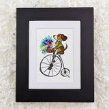 Fancy dog on a penny farthing bike with a basket of flowers, art print with a black frame