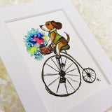 cute dog with a green vest on a bike with a basket of flowers art print with white matte