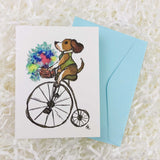 Dog with a green vest on a penny farthing bike with a basket of flowers handmade card with envelope