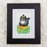 chubby black and white cat sitting on a pumpkin art print with black frame