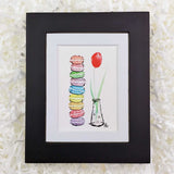 stacked french macaroon cookies and a red tulip art print with a black frame
