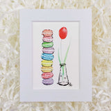 a red tulip and a stack of rainbow french macaron cookies art print with a white matte