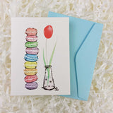 a stack of French Macaron cookies and a red tulip handmade card with an envelope