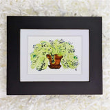 green potted plant with purple and blue flowers art print in a black frame