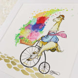 A llama on a penny farthing on a cobblestone road. A basket of flowers towers on the bike. An art print with a white matte