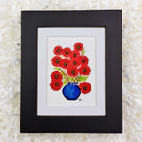 red daisies in a round blue vase art print with black frame