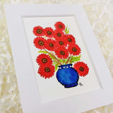 cute red daisies in a dark blue vase with a white matte