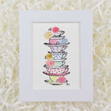 a stack of colorful teacups with roses and crystals art print with white matte