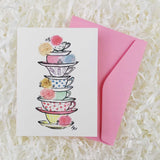 A stack of colorful teacups with roses handmade card and envelope