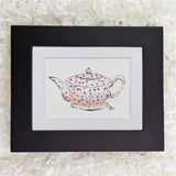 white teapot with pink and purple scattered flowers art print with black frame