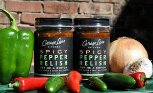 Two bottles of Get Me A Switch Spicy Pepper Relish with fresh ingredients