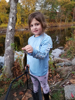 Little girl wearing a fishing shirt holding a fish and fishing net.