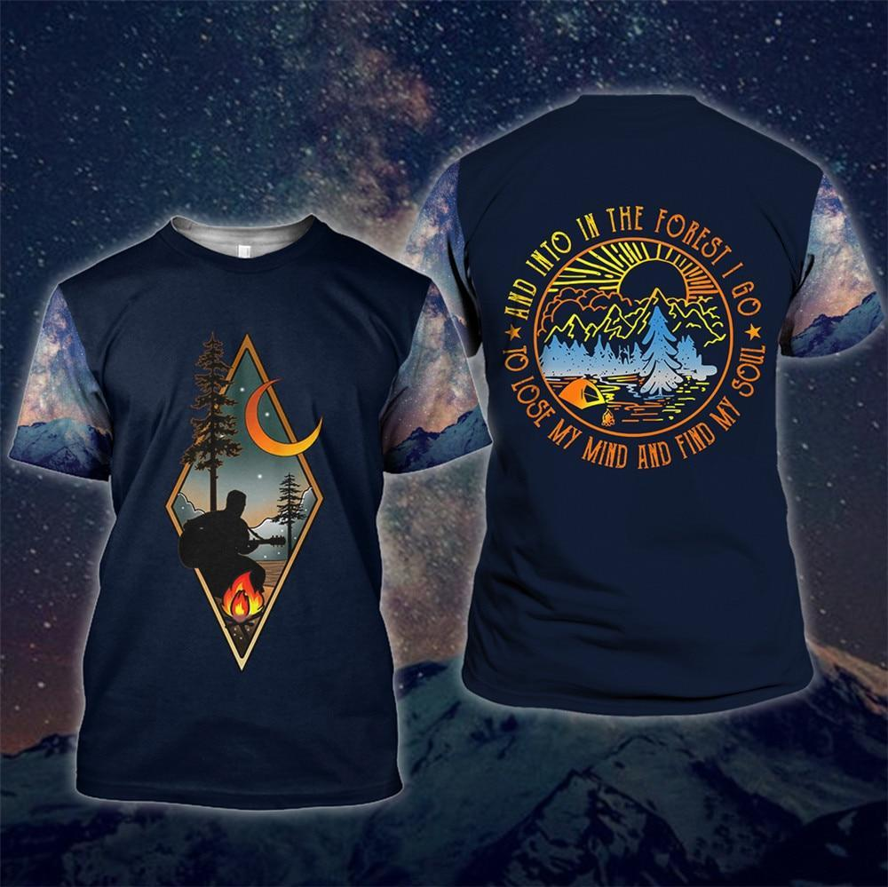 Men's blue camping shirt with man playing guitar around the fire. Text on the back saying And into the forest I go to lose my mind and find my soul.