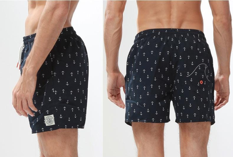 Side and back view of man wearing anchor print beach shorts.