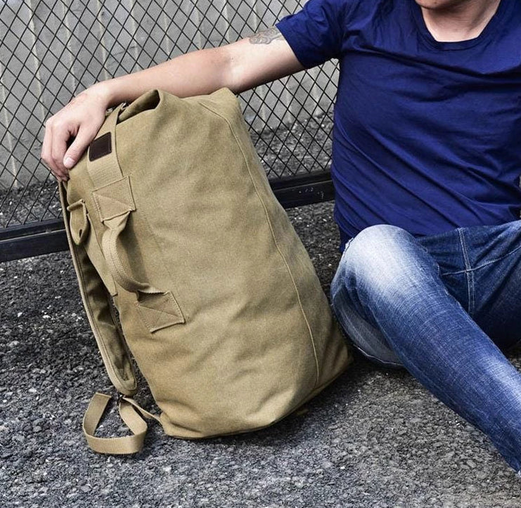 Male model sitting with the canvas rucksack next to him on the ground.