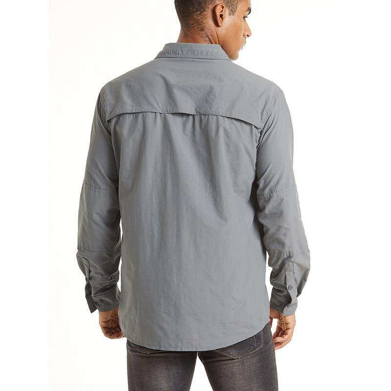 Male wearing a grey button up long sleeve shirt that has ventilation opening on the back.