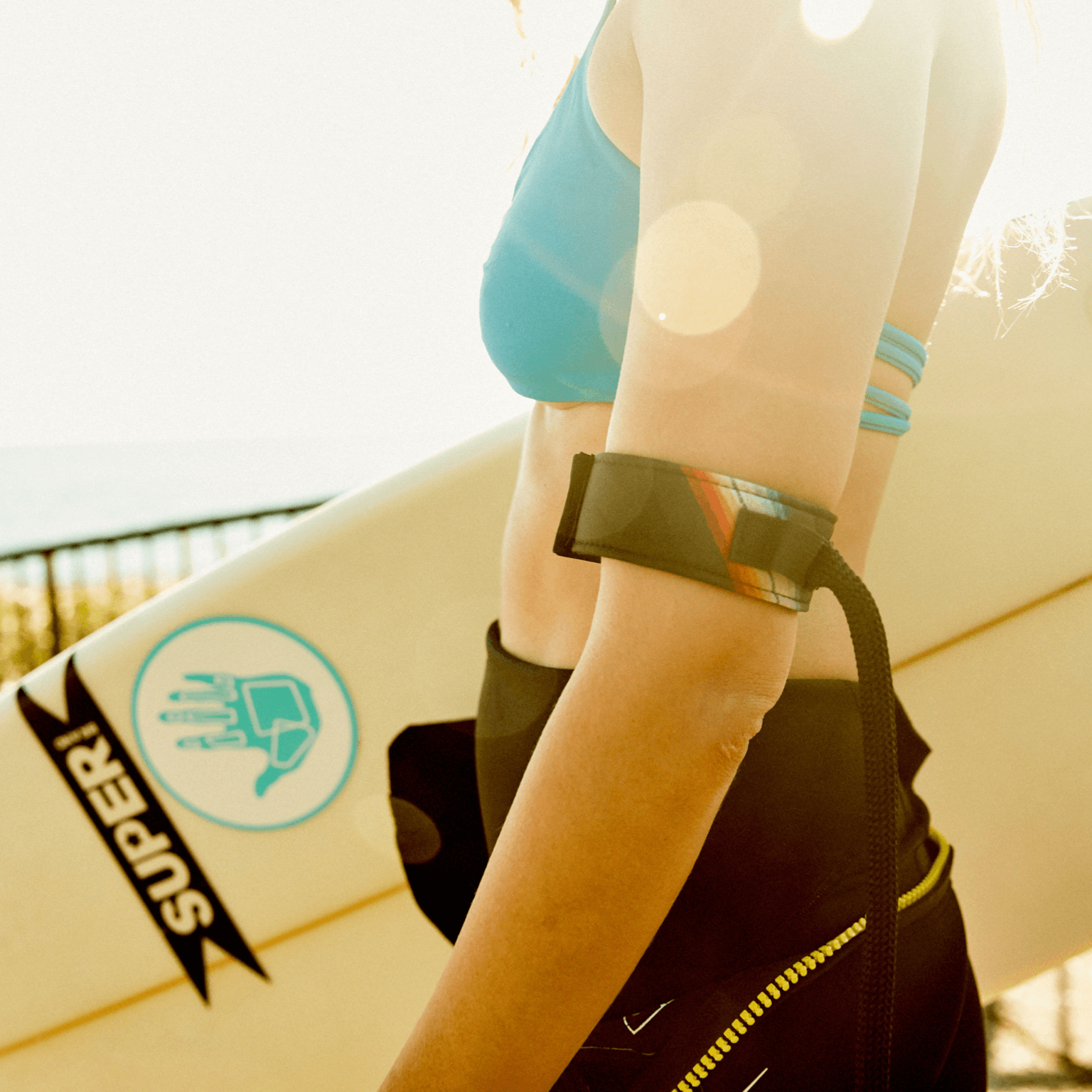Female surfer wearing the Bingin Dog 'Back in Black' velcro dog leash handle around left arm while holder her surfboard.