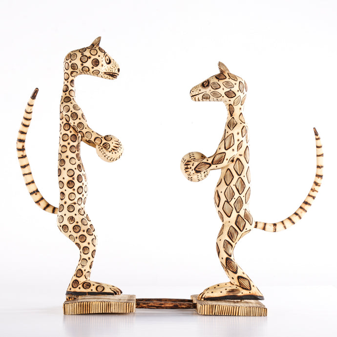 Two Standing Wooden Animals Holding Balls in their Paws