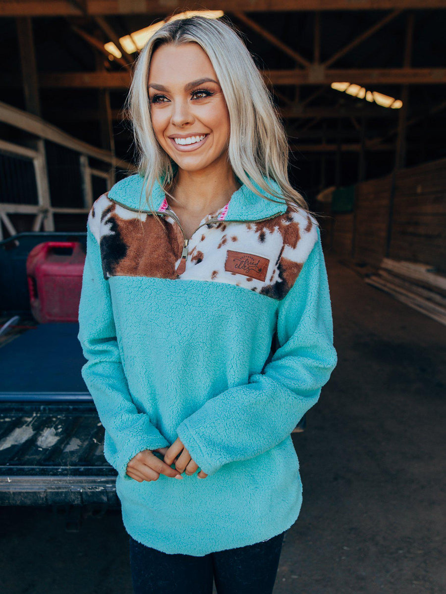 turquoise sherpa pulloever with black and brown cow print design