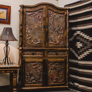 <p><span>Western luxury at its best, </span><span>this real wood Armoire will be the centre piece in your Ranch or modern-country home.</span></p> <p>Handcrafted in solid Mexican reclaimed wood with a smoky-amber finish this majestic Armoire features hand tooled verdigris copper panels, Western-style carved wood accents and forged-iron hardware. Crafted by Mexican Artisans, the copper is skilfully hammered by hand then treated to create this stunning finish.</p>