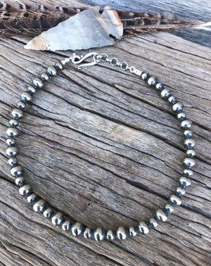 "These are genuine Navajo Pearls, handmade by artists who have been making these pearls for generations. Each Pearl bead is plated in .925 sterling silver, antiqued & polished creating a shimmering, perfect Navajo pearl!  This gorgeous design is the 14"" length with 6mm and 8mm Navajo Pearls. Finished with s-clasp and adjustable chain in silver. Stunning short - choker style necklace!"