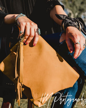 On trend sexy mustard tan. The signature Lakoda clutch, grande size to carry all your 'on the go' essentials in style. Roxy West Collection Be unique, be an original Handcrafted for us in Europe by leather artisan maker  Beautifully soft genuine leather with raw edge flap Flap folds over for easy access Leather feather tassel and leather wristlet Zipper closure with raw leather inner and slot pocket  Antique hardware completes each look Approx size 27x23cm