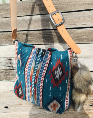 How gorgeous is this latest design!  THE BAG - The real deal. Genuine wool Saddleblanket with that beautiful colour and stunning Southwest design. Sourced by us from El Paso TX.  THE STRAP- Embossed 'floral design' natural leather belt strap with vintage western buckle, that's adjustable to suit your style. The leather has been lightly hand-stained to keep its natural patina & hand-stitched to bag by our leather maker here in Australia.  Silver/brass hardware and clip on foxtail completes the look.