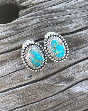 "The Stones. Gorgeous 100% natural turquoise in azure blue with golden tan matrix from the Sierra Nevadas.   Bright blue 100% natural turquoise cabochon size 18x15mm each.  Stamped .925 sterling silver, artisan crafted in New Mexico. This incredible pair of earrings measure .75"" in length including the sterling silver etched setting. Post studs with artisan backs."