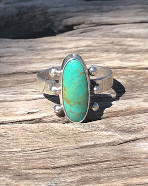 The Stone: A natural Royston Turquoise gem with a full matrix of green azure and earthy-gold webbing.  The Ring: Statement oval shape in .925 silver with Southwest silver work on simple silver band. Artisan crafted with genuine USA/Arizona Turquoise. 'One of a kind'.  Custom-made by talented silver-maker in QLD Australia. Small size 6.5_ AUS M